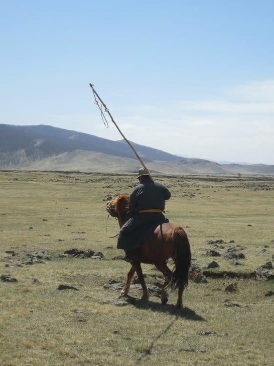 Un des éleveurs qui nous accompagne pour la transhumance veille à ce qu'aucun des moutons se fasse la belle à l'aide de son lasso