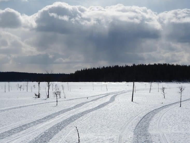 Les traces de moto neige sous le soleil de Laponie