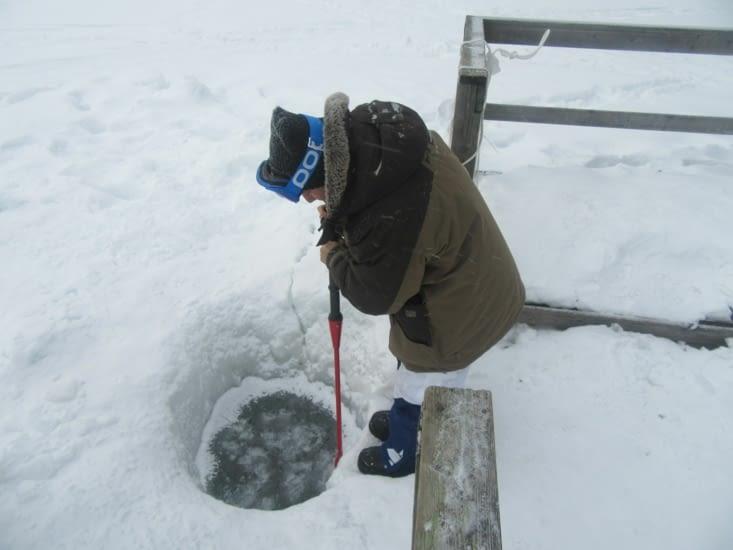 Victor prépare le trou dans le lac pour la baignade post sauna