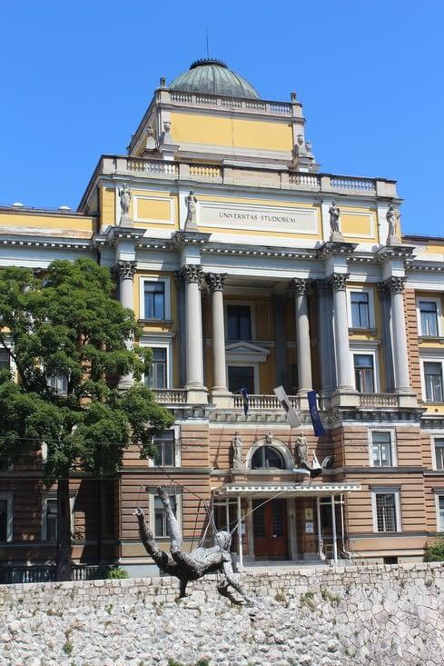 Faculté de droit avec devant au dessus de l'eau des sculptures en métal en lévitation