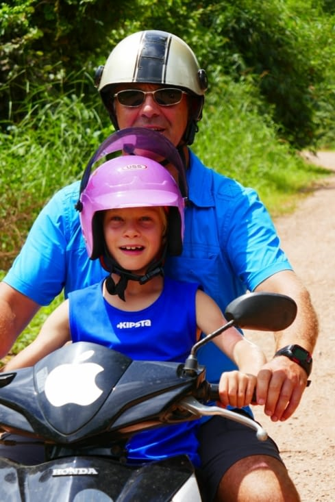 Maël prend une leçon de conduite en scooter sur la piste.