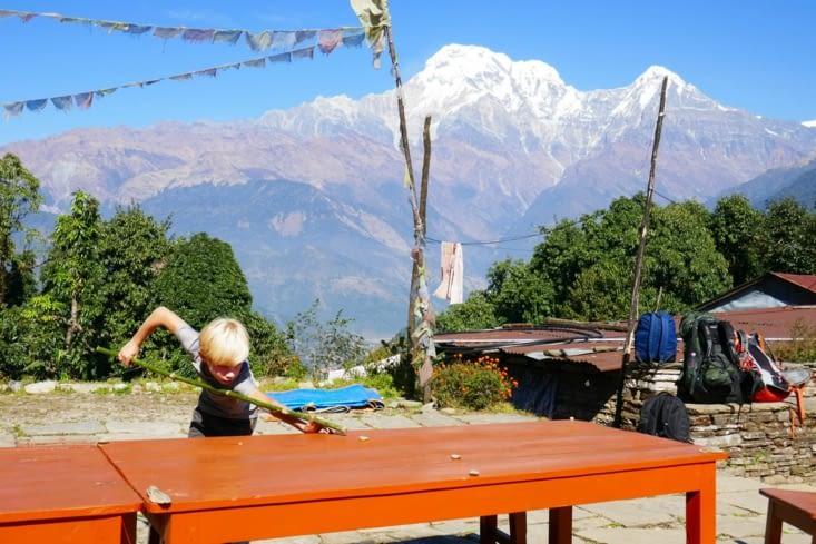 Maël se crée un billard avec des cailloux sur une table et un bâton en guise  de queue