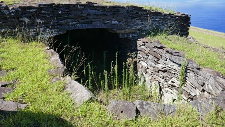 Une habitation dont le toit n'a été que partiellement reconstruit pour montrer l'intérieur