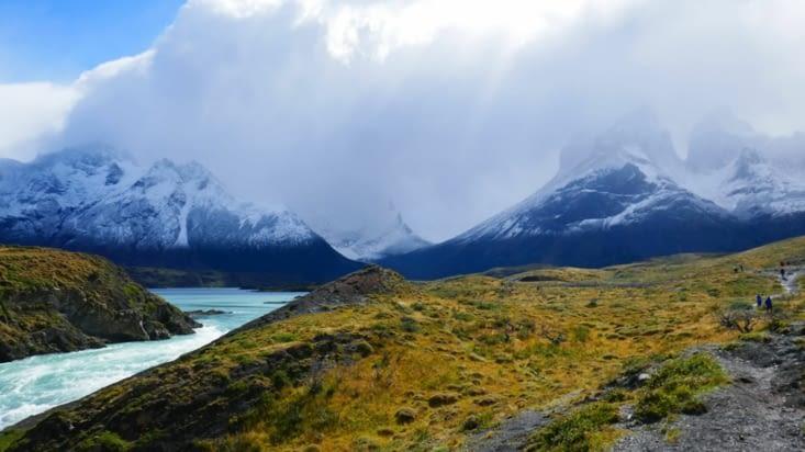 Contraste entre les couleurs des prairies et le noir et blanc des montagnes enneigées