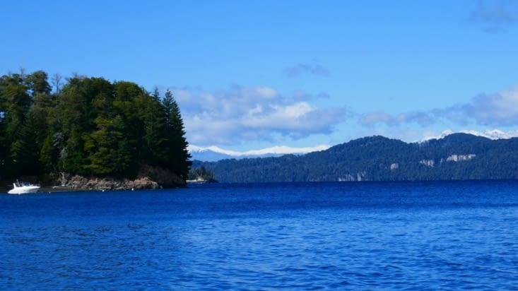 Pause près d'un lac d'un bleu profond avec les montagnes enneigées derrière