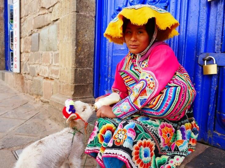 Péruvienne en habit traditionnel et son jeune lama: une pièce contre la photo. ..
