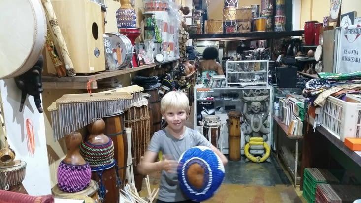 Maël teste une énorme maracas dans un magasin de musique