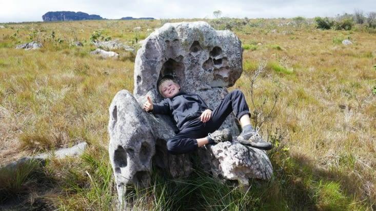 Maël  fait une pause dans un fauteuil de roi en pierre
