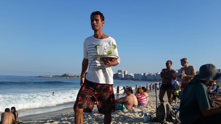 Les marchands ambulants font leur dance commerciale autour des serviettes de plages