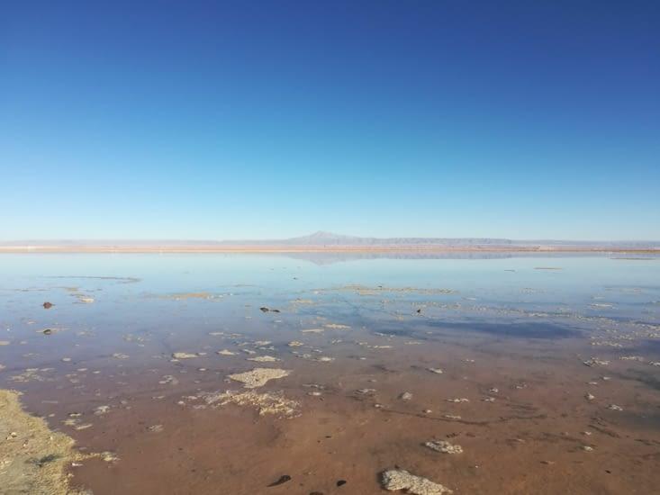 Au désert de sel, les montagnes se reflètent dans le lac.