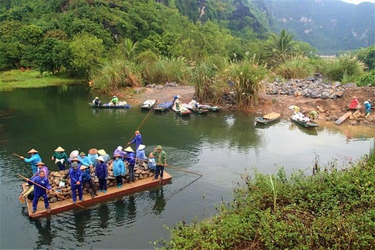 Sur la route, on croise des travailleurs sur la rivière. Ils sont bien chargés !