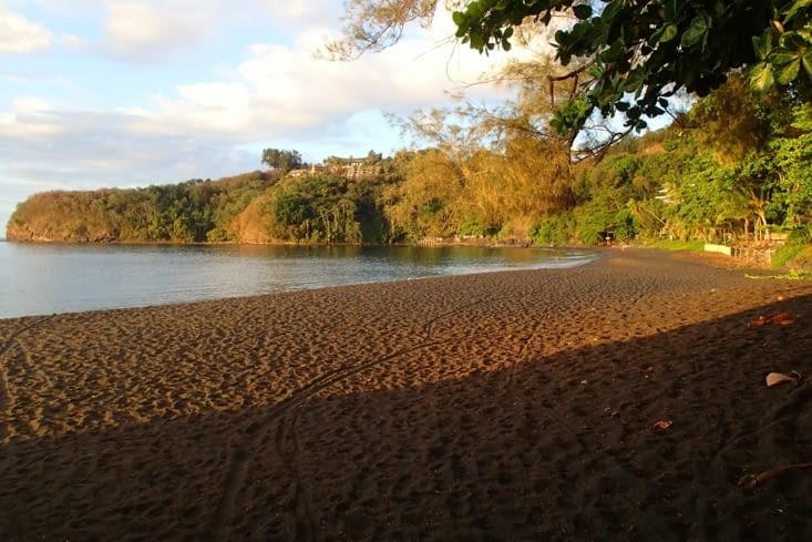 Un dernier bain au coucher du soleil sur une plage de sable noir.
