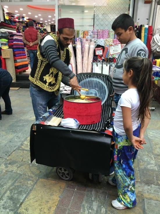 Un artisan qui propose des sucettes faites en direct ! Avec en carriole une poussette d'enfant !
