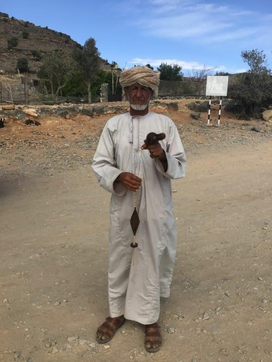 L'homme file La laine des moutons tout en essayant de nous parler
