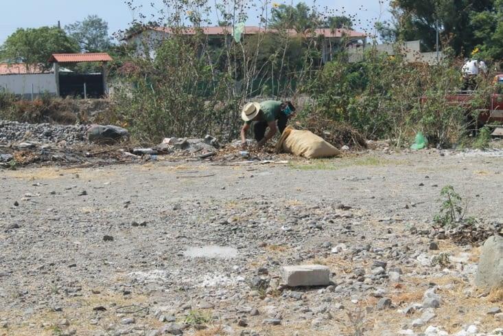 Un monsieur qui tri les déchets du bord de rivière