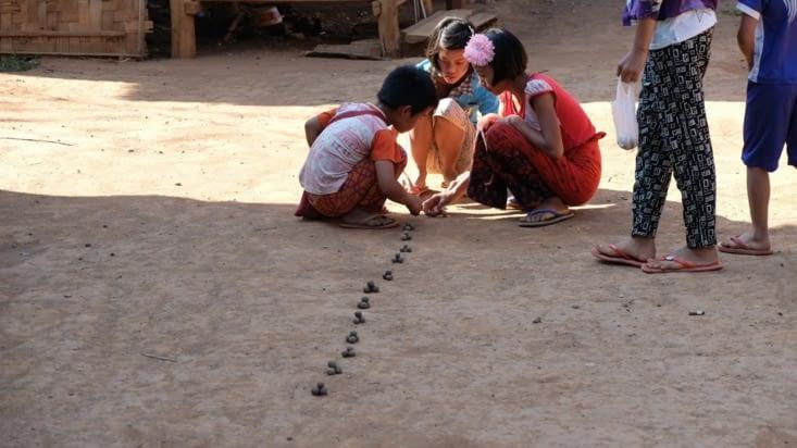 Des enfants qui jouaient aux billes en argiles dans un village de passage