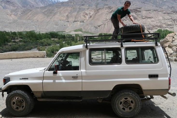 Virgile fixe les roues de secours sur le toit de notre jeep