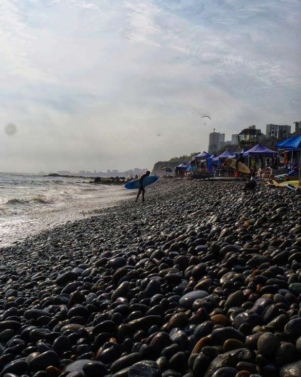 Surfeur de Lima sur sa plage de galets